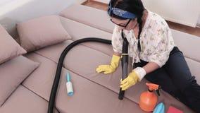 Καθαρίζοντας καναπές γυναικών με την ηλεκτρική σκούπα απόθεμα βίντεο