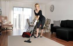 Καθαρίζοντας κυρία που σκουπίζει με ηλεκτρική σκούπα στο εσωτερικό Στοκ Εικόνες
