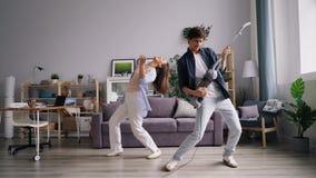 Καθαρίζοντας πάτωμα ατόμων με την ηλεκτρική σκούπα που χορεύει με τη φίλη που έχει τη διασκέδαση φιλμ μικρού μήκους