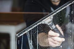 καθαρίζοντας παράθυρο επιφάνειας γυαλιού εστίασης στοκ εικόνα