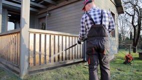 Καθαρίζοντας πεζούλι ατόμων με ένα πλυντήριο δύναμης - καθαριστής πίεσης απόγειου στο ξύλινο κιγκλίδωμα πεζουλιών απόθεμα βίντεο