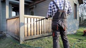 Καθαρίζοντας πεζούλι ατόμων με ένα πλυντήριο δύναμης - καθαριστής πίεσης απόγειου στο ξύλινο κιγκλίδωμα πεζουλιών φιλμ μικρού μήκους