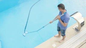 Καθαρίζοντας πισίνα ατόμων με τον κενό καθαριστή σωλήνων νωρίς το πρωί απόθεμα βίντεο