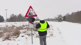Καθαρίζοντας προειδοποιητικό σημάδι εργαζομένων από το χιόνι κοντά στο δρόμο απόθεμα βίντεο