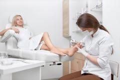 Καθαρίζοντας πόδι γιατρών Podiatrist από τον κάλο Στοκ Εικόνες