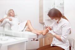 Καθαρίζοντας πόδι γιατρών Podiatrist από τον κάλο Στοκ φωτογραφία με δικαίωμα ελεύθερης χρήσης