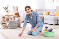 Καθαρίζοντας τάπητας νοικοκυρών ενώ τα παιδιά της στοκ φωτογραφία με δικαίωμα ελεύθερης χρήσης