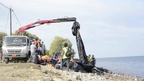 Καθαρίζοντας την παραλία από τα υλικά που αφήνονται από τους πρόσφυγες απόθεμα βίντεο