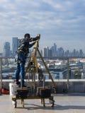 Καθαρίζοντας υπάλληλος παραθύρων με τα εργαλεία εργασίας και το υπόβαθρο πόλεων Στοκ Φωτογραφία