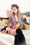 Καθαρίζοντας υπηρεσία: όμορφος λίγο σκυλί με την κόκκινη συνεδρίαση κορδελλών με το κορίτσι pinup στο κρεβάτι που εξετάζει σοβαρά Στοκ Φωτογραφίες