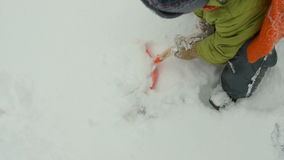 Καθαρίζοντας χιόνι παιδιών με το φτυάρι παιχνιδιών απόθεμα βίντεο