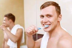 Καθαρίζοντας δόντια ατόμων μπροστά από τον καθρέφτη Στοκ Φωτογραφία