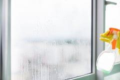 Καθαρίζοντας suds σαπουνιών εργαζομένων στο παράθυρο γυαλιού με το ελαστικό μάκτρο και το κουρέλι στοκ φωτογραφίες