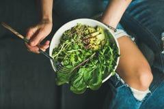 Καθαρίστε την κατανάλωση του προγεύματος με το σπανάκι, το arugula, το αβοκάντο, τους σπόρους και τους νεαρούς βλαστούς Στοκ Φωτογραφίες