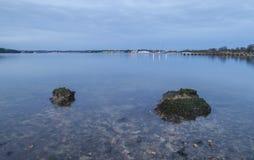 Καθαρίστε το νερό στον κόλπο με τους βράχους και τα φω'τα στο σούρουπο Στοκ Φωτογραφίες