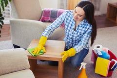 Καθαρίστρια που καθαρίζει προσεκτικά με το μικρό τραπεζάκι σαλονιού σφουγγαριστρών Στοκ εικόνα με δικαίωμα ελεύθερης χρήσης