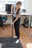 Καθαρισμός διαμερισμάτων Ένα νέο ευρωπαϊκό κορίτσι που σκουπίζει ένα δωμάτιο με ηλεκτρική σκούπα Στοκ Φωτογραφίες