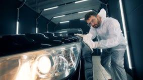 Καθαρισμός ενός μαύρου αυτοκινήτου που πραγματοποιείται από έναν άνδρα εργαζόμενος απόθεμα βίντεο
