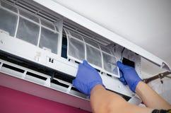 Καθαρισμός κλιματιστικών μηχανημάτων Το άτομο ελέγχει το φίλτρο Στοκ Εικόνες