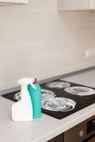 Καθαρισμός σπιτιών - πλαστικά μπουκάλια με τα απορρυπαντικά tabletop κουζινών στο υπόβαθρο των ηλεκτρικών σομπών Καθαρισμός της ε Στοκ εικόνες με δικαίωμα ελεύθερης χρήσης
