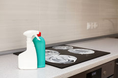 Καθαρισμός σπιτιών - πλαστικά μπουκάλια με τα απορρυπαντικά tabletop κουζινών στο υπόβαθρο των ηλεκτρικών σομπών Καθαρισμός της ε Στοκ φωτογραφία με δικαίωμα ελεύθερης χρήσης