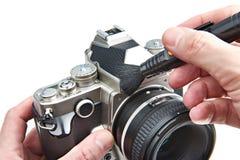 Καθαρισμός της φωτογραφικής DSLR κάμερας σωμάτων με τη βούρτσα στοκ εικόνες