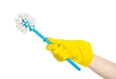 Καθαρισμός του σπιτιού και καθαρισμός της τουαλέτας: ανθρώπινο χέρι που κρατά μια μπλε βούρτσα τουαλετών στα κίτρινα προστατευτικ Στοκ φωτογραφία με δικαίωμα ελεύθερης χρήσης