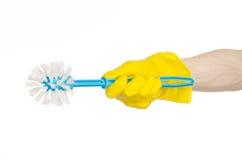 Καθαρισμός του σπιτιού και καθαρισμός της τουαλέτας: ανθρώπινο χέρι που κρατά μια μπλε βούρτσα τουαλετών στα κίτρινα προστατευτικ Στοκ Φωτογραφίες