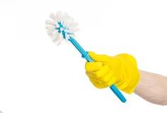 Καθαρισμός του σπιτιού και καθαρισμός της τουαλέτας: ανθρώπινο χέρι που κρατά μια μπλε βούρτσα τουαλετών στα κίτρινα προστατευτικ Στοκ εικόνες με δικαίωμα ελεύθερης χρήσης
