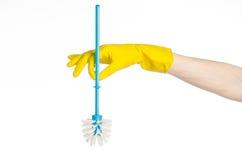 Καθαρισμός του σπιτιού και καθαρισμός της τουαλέτας: ανθρώπινο χέρι που κρατά μια μπλε βούρτσα τουαλετών στα κίτρινα προστατευτικ Στοκ Εικόνες