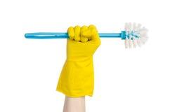 Καθαρισμός του σπιτιού και καθαρισμός της τουαλέτας: ανθρώπινο χέρι που κρατά μια μπλε βούρτσα τουαλετών στα κίτρινα προστατευτικ Στοκ Εικόνα