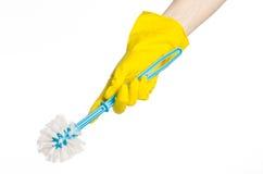 Καθαρισμός του σπιτιού και καθαρισμός της τουαλέτας: ανθρώπινο χέρι που κρατά μια μπλε βούρτσα τουαλετών στα κίτρινα προστατευτικ Στοκ εικόνα με δικαίωμα ελεύθερης χρήσης