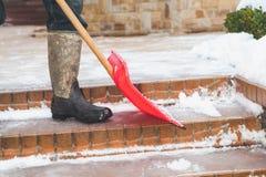 Καθαρισμός των βημάτων σκαλοπατιών από το φτυάρι χιονιού πλαστικών Στοκ φωτογραφίες με δικαίωμα ελεύθερης χρήσης