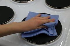 Καθαρισμός των ηλεκτρικών φούρνων με ένα μαλακό ύφασμα Στοκ Φωτογραφίες