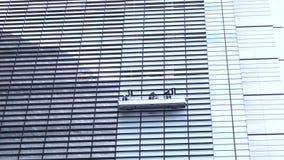 Καθαρισμός των παραθύρων του σύγχρονου κτιρίου γραφείων ουρανοξυστών γυαλιού απόθεμα βίντεο