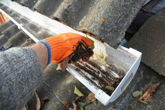 Καθαρισμός υδρορροών βροχής από τα φύλλα το φθινόπωρο με το χέρι Καθαρίζοντας άκρες υδρορροών στεγών Καθαρίστε τις υδρορροές σας  Στοκ φωτογραφία με δικαίωμα ελεύθερης χρήσης