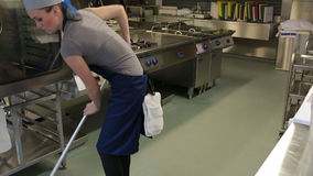 Καθαριστής μιας κουζίνας που σκουπίζει το πάτωμα φιλμ μικρού μήκους