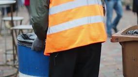Καθαριστής οδών που συλλέγει τα απορρίματα από το φασόλι απορριμμάτων, άτομο που κάνει τη χαμηλόμισθη εργασία χαμαληδίκων απόθεμα βίντεο