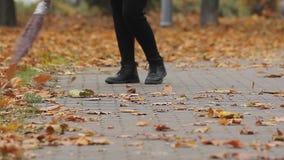 Καθαριστής οδών στις shabby μπότες που σκουπίζουν τα ξηρά φύλλα στο πάρκο φθινοπώρου, χαμηλόμισθη εργασία απόθεμα βίντεο