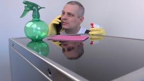 Καθαριστής που μιλά στο έξυπνο τηλέφωνο κοντά στην επιφάνεια της ηλεκτρικής κουζίνας απόθεμα βίντεο