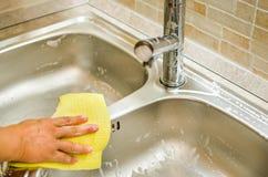 Καθαροί νεροχύτης και στρόφιγγα χεριών γυναικών που χρησιμοποιούν το κίτρινο σφουγγάρι Στοκ Φωτογραφία