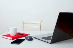 Καθαρός εργασιακός χώρος με το lap-top, το τηλέφωνο, το σημειωματάριο, το φλυτζάνι καφέ και το ποντίκι υπολογιστών Στοκ εικόνες με δικαίωμα ελεύθερης χρήσης