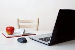 Καθαρός εργασιακός χώρος με το lap-top, το τηλέφωνο, το σημειωματάριο, το φλυτζάνι καφέ και το ποντίκι υπολογιστών Στοκ φωτογραφία με δικαίωμα ελεύθερης χρήσης