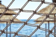 Καθαρός φράκτης ομπρέλες στις όμορφους παραθαλάσσιων θερέτρων, τη θάλασσα και τον ουρανό ι στοκ φωτογραφία