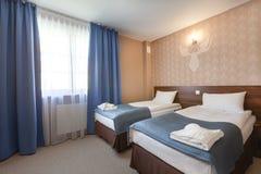 Καθαρό εσωτερικό του δωματίου ξενοδοχείου με το κρεβάτι Στοκ Φωτογραφίες