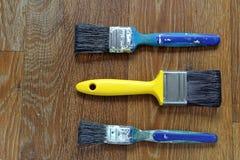 Καθαρό κίτρινο πινέλο με τις βρώμικες μπλε βούρτσες στοκ εικόνες