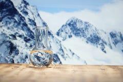 Καθαρό νερό σε μια εργαστηριακή φιάλη γυαλιού στον ξύλινο πίνακα στο υπόβαθρο χειμερινών βουνών Οικολογική έννοια, η δοκιμή στοκ εικόνες με δικαίωμα ελεύθερης χρήσης