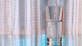Καθαρό πόσιμο νερό που χύνεται σε ένα γυαλί κίνηση αργή φιλμ μικρού μήκους
