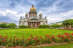 Καθεδρικός ναός του ST Isaac ` s στο νεφελώδη καιρό με τα λουλούδια Στοκ Εικόνα