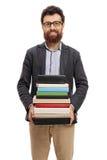 Καθηγητής με έναν σωρό των βιβλίων που εξετάζουν τη κάμερα Στοκ Εικόνες